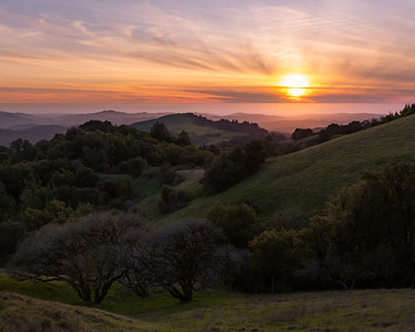 A spring sunset over green hills and the Pacific Ocean