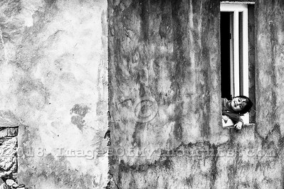 A young girl smiles through a window in the village of Ushguli in Svaneti, Georgia, part of a recognized UNESCO World Heritage Site. Located at an altitude of 2,100 meters near the foot of Shkhara, one of the highest summits of the Greater Caucasus mountains, Ushguli is one of the highest continuously inhabited settlements in Europe. It is home to 70 families and covered in snow for 6 months of the year. Often the road to Mestia is impassable. Ushguli shares the Svaneti region traditional koshki, defensive stone structures built from the 9th century onward and is known for it's architectural treasures and picturesque landscapes.