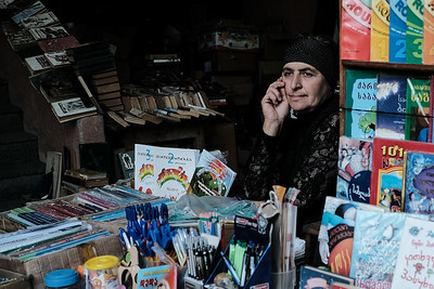 A woman sells books at an outdoor stand in Kutaisi, Georgia.