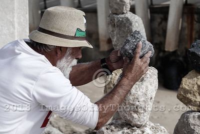 A sculptor balances rocks onto each other to create an art installation along the Tagus or Tejo River.