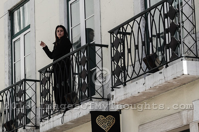 A woman smokes a cigarette on a balcony in Lisbon.