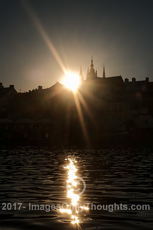 A view of the sun setting over Prague Castle from the Vltava River.
