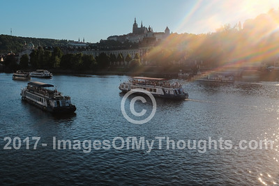 A view of the Vltava River at sunset depicts some of the many boats offering a river cruise.
