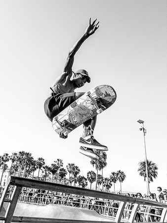 skateboarder jumping with his skateboard over a fence at the Venice Skatepark (California) in a sort of a contest among friends. It is one of the only in the world located on a beach. It features two bowls, a snake run and a street section with steps, rails and platforms