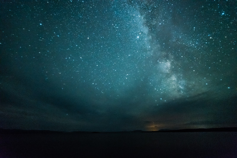Milky Way over Yellowstone Lake. Lights and smoke from the Berry fire can be seen on the horizon