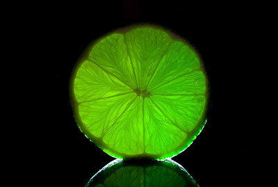 Bright green natural lime on black mirror background