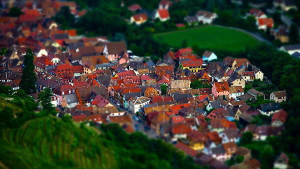 Aerial tilt-shift view of little village in Alsace. Red tile roofs of timber-framing traditional houses.