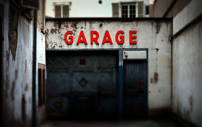 Old abandoned garage with red sign