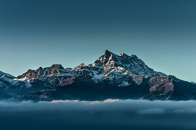 Beautiful alpine peaks view from the top over the clouds, natural landscape