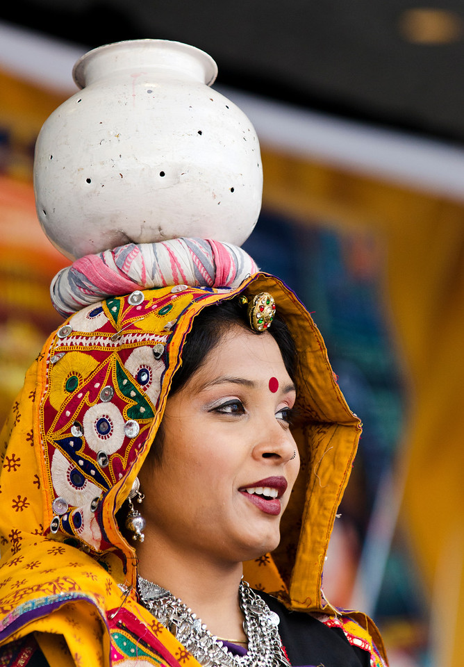 ...skilfully balancing elaborated headdresses on their heads during traditional dances.
