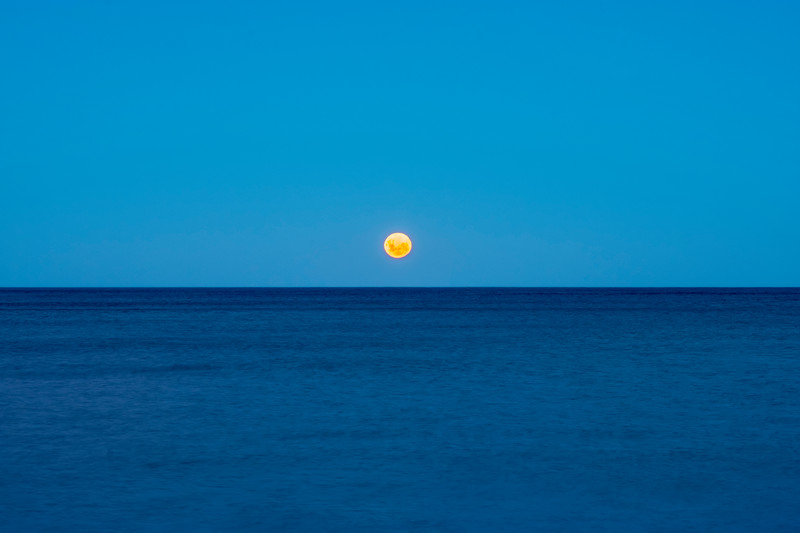 blood moonrise over ocean