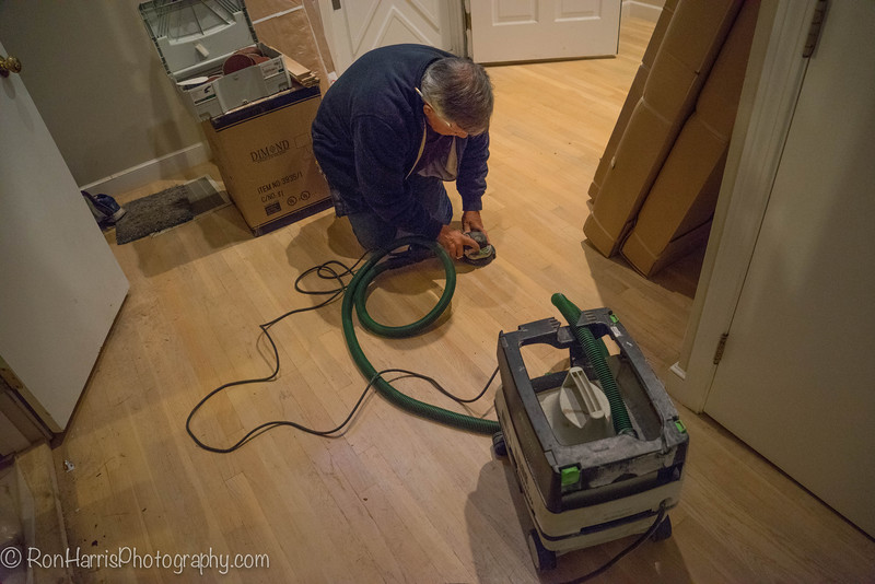 Tommy sanding a spot on the old floor.