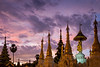 Golden spires of the magnificent Shwedagon Pagoda dominates the city skyline of Yangon at sunset.