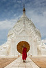 Young monk posing in front of stupa of Hsinbyume Pagoda, Mingun, Myanmar