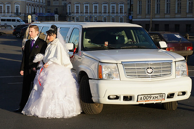 Newly weds with their hired stretched limo