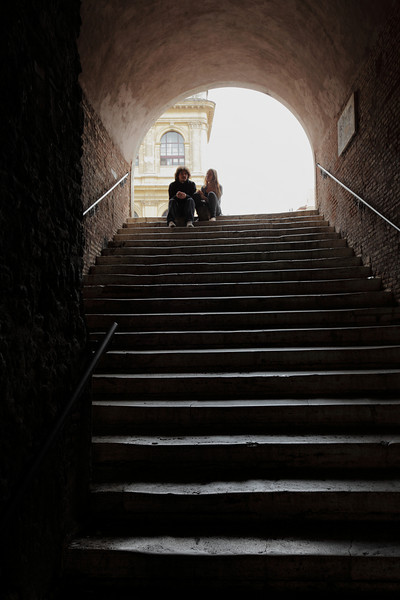 A couple sitting at the top of this stairs