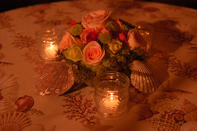 Lovely coral roses and green roses were used with moss to carry out the theme.  300 bottle glass votive candles in a scallop pattern were also used.