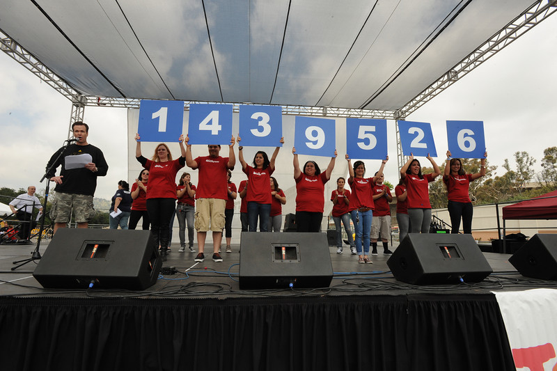 John Ireland announces the total raised at the 2011 Walk Now for Autism Speaks Los Angeles while Team Gap proudly displays the figures for the walk.