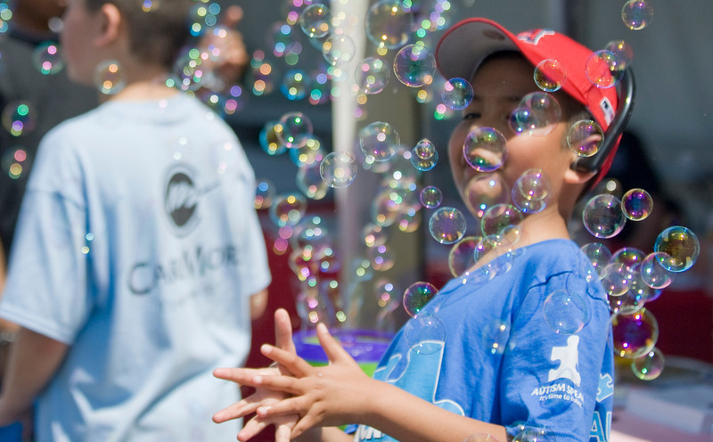 Angel Cruz, 8, of Inglewood plays with bubbles coming from a machine during Saturday's Los Angeles Walk Now for Autism Speaks event at the Rose Bowl.