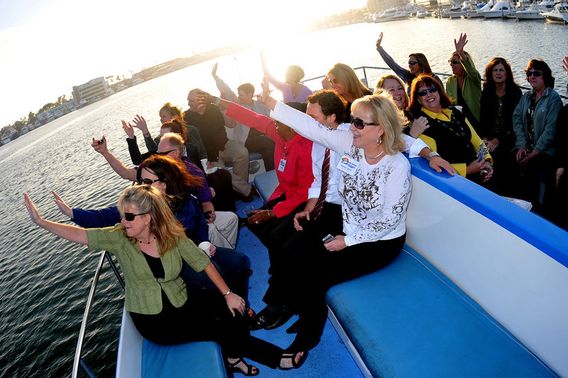 "Photo: Legal Administrators wave to a boat passing by atop the ""Showboat"" during their harbor cruise, Thursday June 17, 2010, in Newport Beach. A group of 18 legal administrators from Orange County law firms enjoyed scenic views of Newport Beach Harbor during the networking event hosted by the Orange County Chapter of the Association of Legal Administrators. Photo by Jess Block/ Current"