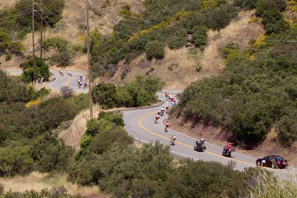 The peloton chases on the technical descent.