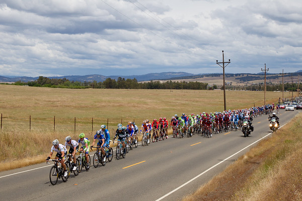 The peloton makes steady pace under friendlier skies,, but there is rain forcast for the finish circuits.
