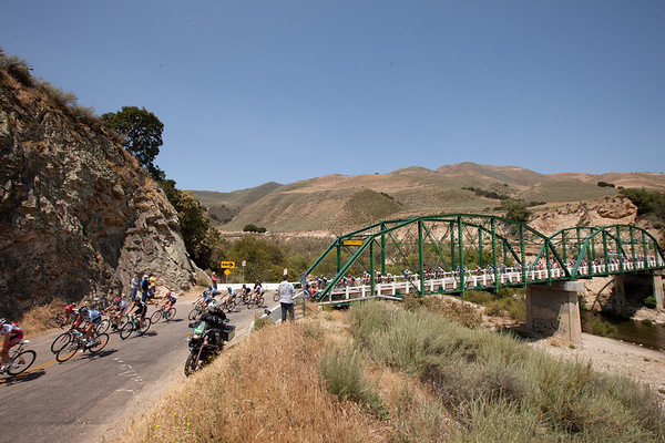 The peloton seems to be enjoying the scenery as they cross a bridge.