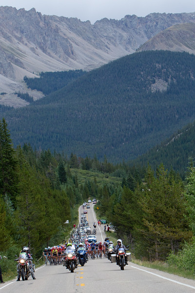 The peloton is dwarfed by the surrounding mountains as they begin the climb of Independence  Pass.