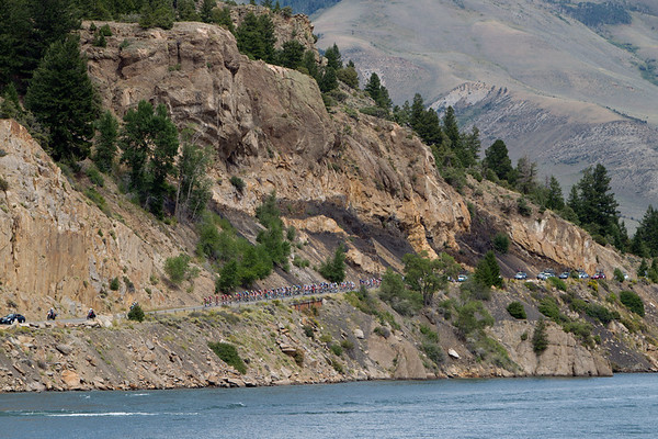 ...with the peloton dwarfed by the rock cliffs above the water.