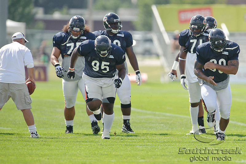 5 August 2010:  Chicago Bears Defensive Coordinator Rod Marinelli (left) runs a drill with defensive linemen Anthony Adams (95) and Julius Peppers (90) during the Bears training camp practice at Olivet Nazarene University in Bourbonnais, IL.<br /> Mandatory Credit - John Rowland / Southcreek Global