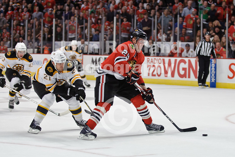 Chicago left wing Bryan Bickell (29) comes in on a breakaway while Boston's Andrew Ference (21) defends during the NHL game between the Chicago Blackhawks and the Boston Bruins at the United Center in Chicago, IL. The Bruins defeated the Blackhawks 3-2 in a shootout.