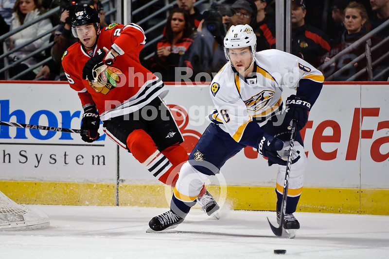 Nashville defenseman Kevin Klein (8) with the puck while Chicago left wing Viktor Stalberg (25) pursues during the NHL game between the Chicago Blackhawks and the Nashville Predators at the United Center in Chicago, IL. The Predators defeated the Blackhawks 3-1.