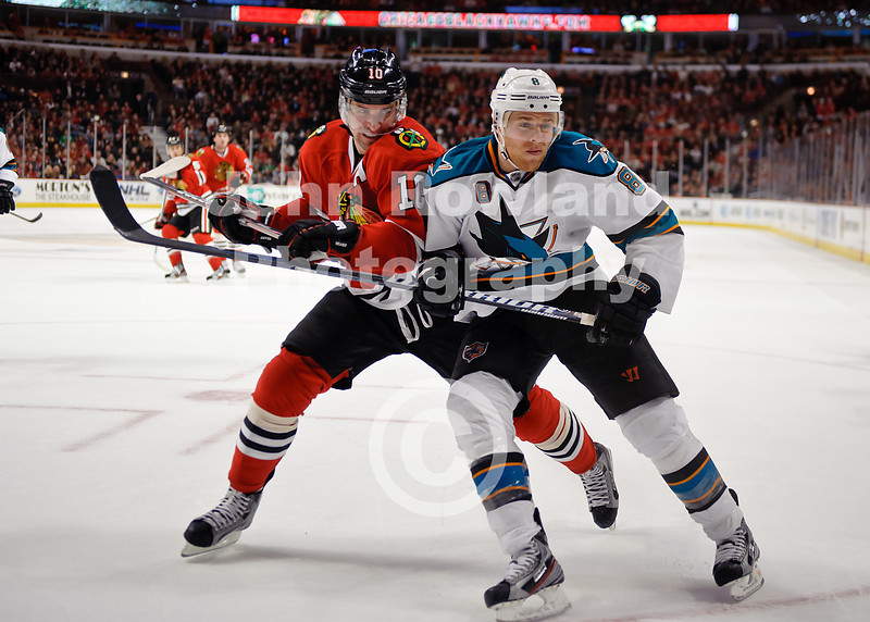 Chicago left wing Patrick Sharp (10) and San Jose center Joe Pavelski (8) battle for the puck during the NHL game between the Chicago Blackhawks and the San Jose Sharks at the United Center in Chicago, IL. The Blackhawks defeated the Sharks 3-2 in overtime.