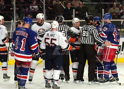 NEW YORK, Feb. 19 — New York Rangers captain Mark Messier (11) and New York Islanders forward Jason Blake watch as officials break up a fight, Thursday night at Madison Square Garden. The Rangers won 6-2.