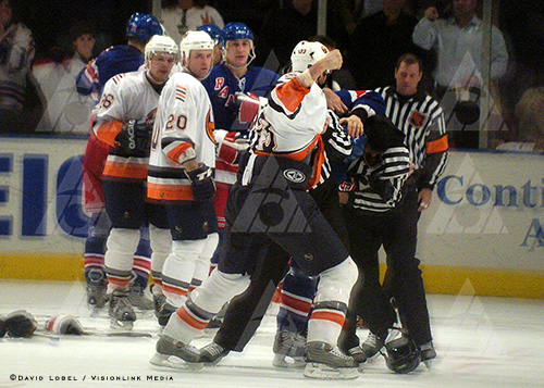 NEW YORK, Feb. 19 — Officials break up a fight during a game between the New York Rangers and New York Islanders, Thursday night at Madison Square Garden.
