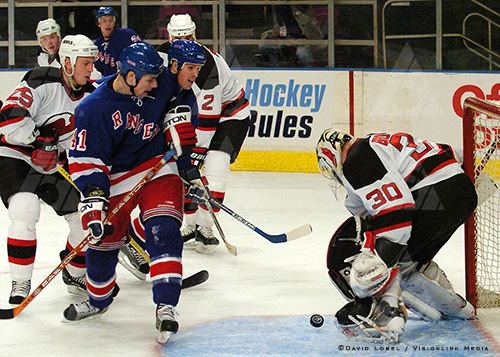 NEW YORK, Feb. 21, 2004 — New Jersey Devils goaltender Martin Brodeur tries to get a handle on a bouncing puck as New York Rangers forward Jed Ortmeyer watches, during the Devils' 7-3 win, Saturday at Madison Square Garden.