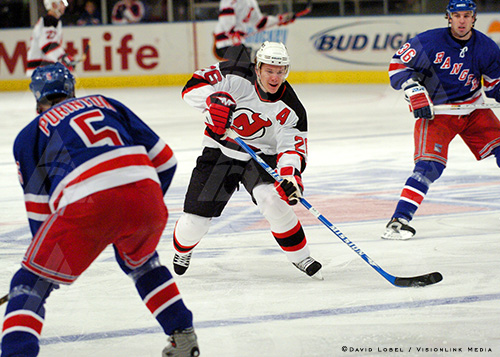 NEW YORK, Feb. 21, 2004 — New Jersey Devils center Patrick Elias moves the puck across the blue line, Saturday afternoon during a 7-3 Devils win, as New York Rangers defenders Dale Purinton (5) and Matthew Barnaby (36) watch, Saturday at Madison Square Garden.