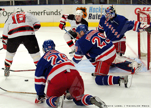 NEW YORK, Feb. 21, 2004 — New York Rangers defenders Martin Rucinsky (26) and Boris Mironov (29) get down in front of goaltender Mike Dunham as the puck scoots away from New Jersey Devils forward Sergei Brylin, during the Devils' 7-3 win, Saturday afternoon at Madison Square Garden.