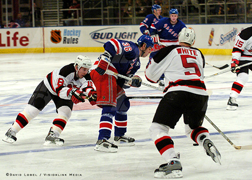 NEW YORK, Feb. 21, 2004 — New Jersey Devils center Serge Brylin ducks behind New York Rangers winger Matthew Barnaby and fires in a shot from the blue line, during the Devils' 7-3 win, Saturday at Madison Square Garden.