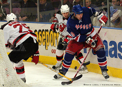 NEW YORK, Feb. 21, 2004 — New York Rangers left winger Dan LaCouture works with a bouncing puck behind the net, against two New Jersey Devils defenders, during a 7-3 loss, Saturday at Madison Square Garden.