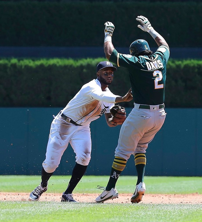 . Detroit Tigers second baseman Niko Goodrum tags Oakland Athletics\' Khris Davis at second before throwing out Matt Olson (28) at first during the third inning of a baseball game, Thursday, June 28, 2018, in Detroit. (AP Photo/Carlos Osorio)