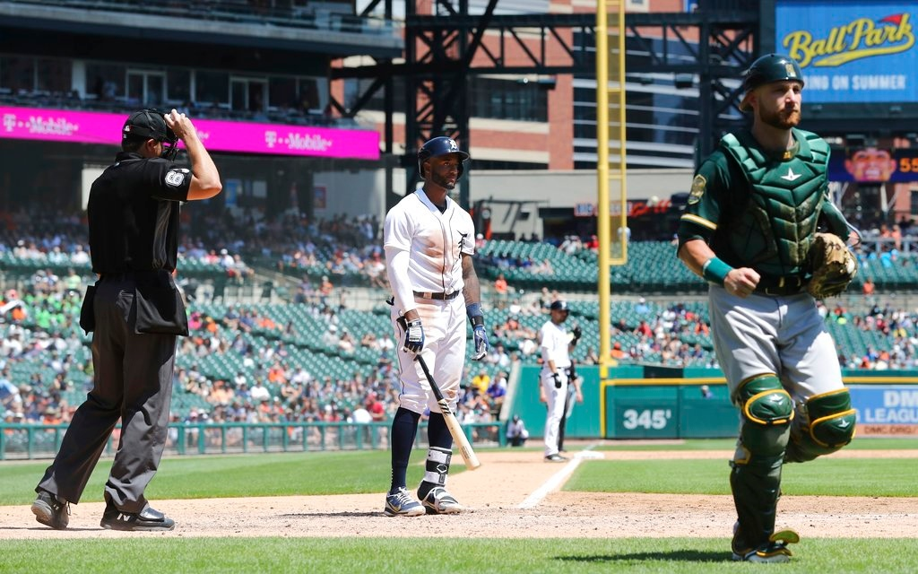 . Oakland Athletics catcher Jonathan Lucroy runs back to the dugout and home plate umpire Ryan Additon throws the ball to Athletics pitcher Sean Manaea as Detroit Tigers\' Niko Goodrum stands at home plate after striking out with the bases loaded during the sixth inning of a baseball game, Thursday, June 28, 2018, in Detroit. (AP Photo/Carlos Osorio)
