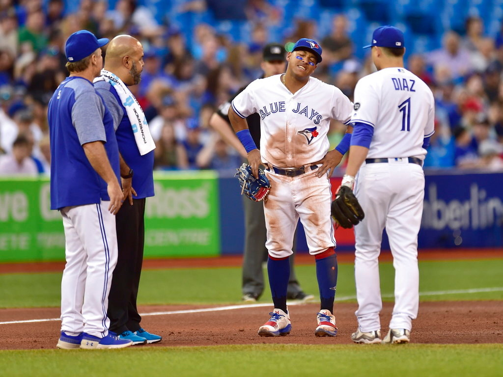 . Toronto Blue Jays shortstop Aledmys Diaz (1), manager John Gibbons, left, and a trainer check on second baseman Yangervis Solarte during the sixth inning of a baseball game against the Detroit Tigers on Friday, June 29, 2018, in Toronto. (Frank Gunn/The Canadian Press via AP)