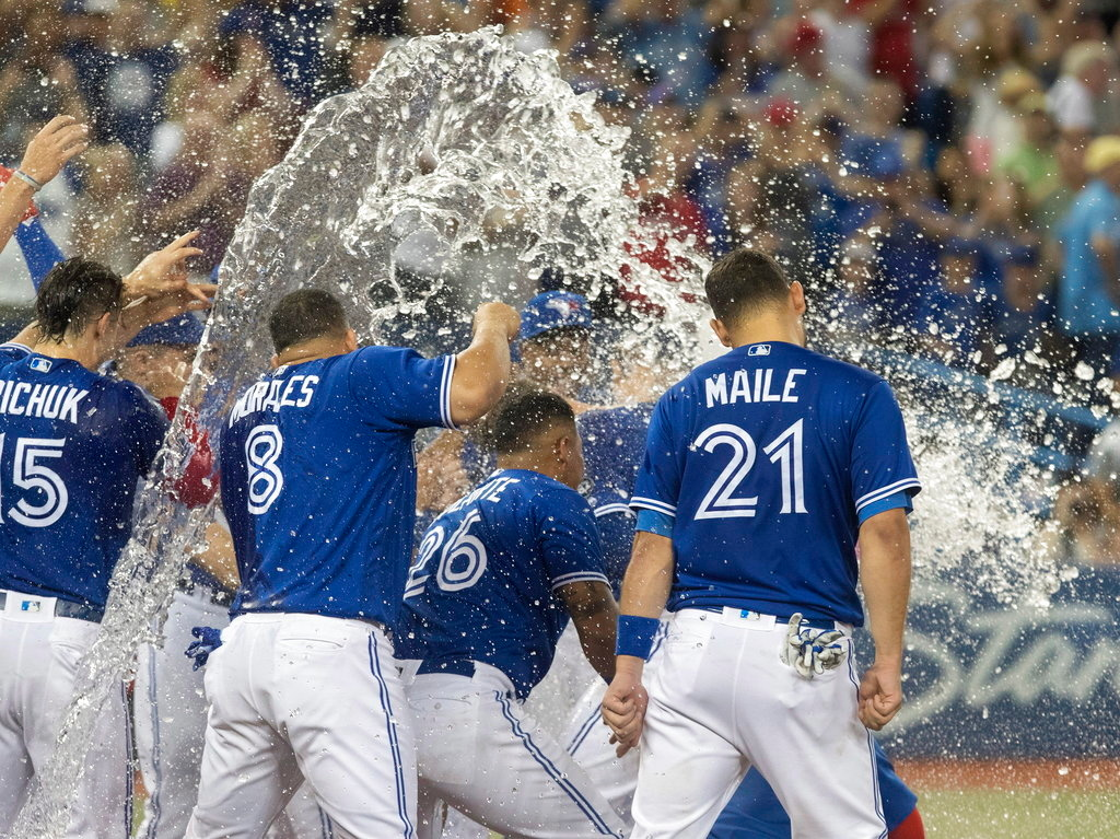 . Toronto Blue Jays\' Justin Smoak, hidden is doused by teammates as he reaches home plate after hitting the game-winning home run defeat the Detroit Tigers 4-3 in the ninth inning of a baseball game in Toronto on Saturday, June 30, 2018. (Fred Thornhill/The Canadian Press via AP)