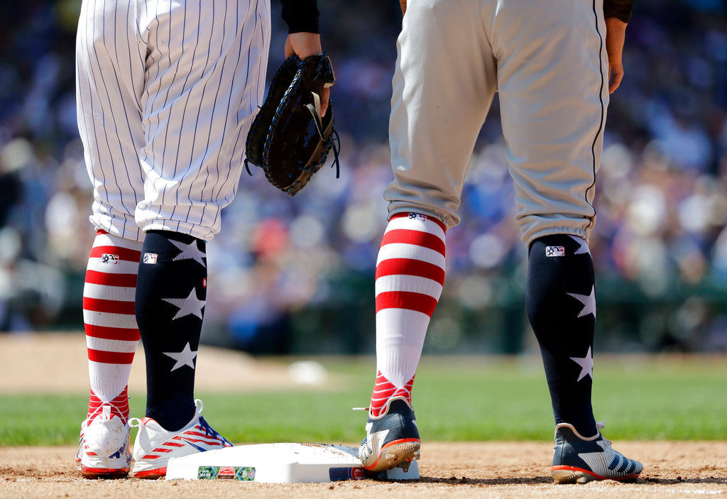 . Chicago Cubs first baseman Anthony Rizzo, left, and baserunner, Detroit Tigers\' Mikie Mahtook sport identical patriotic stockings during the fifth inning of a baseball game Tuesday, July 3, 2018, in Chicago. (AP Photo/Charles Rex Arbogast)