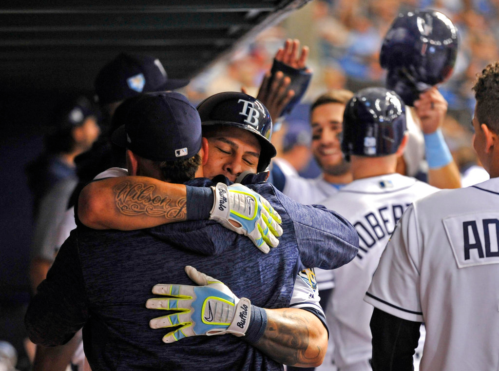 . Tampa Bay Rays\' Jesus Sucre, left, hugs Wilson Ramos in the dugout as teammates celebrate Ramos\' three-run home run off Detroit Tigers starter Matthew Boyd during the third inning of a baseball game Tuesday, July 10, 2018, in St. Petersburg, Fla. (AP Photo/Steve Nesius)