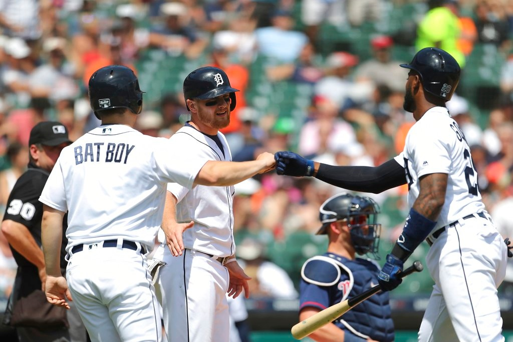 . Detroit Tigers\' John Hicks, center, waits on Niko Goodrum, right, at home plate after Hicks scored on Goodrum\'s sacrifice during the seventh inning of a baseball game against the Minnesota Twins, Thursday, June 14, 2018, in Detroit. (AP Photo/Carlos Osorio)