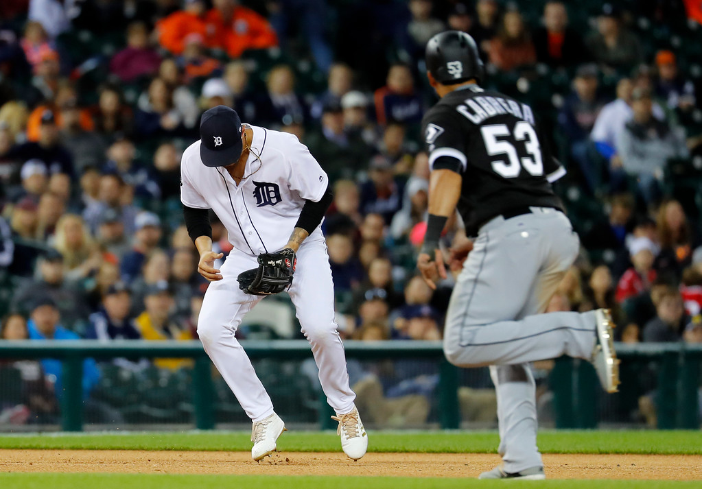 . Detroit Tigers third baseman Nicholas Castellanos (9) loses the ball as Chicago White Sox left fielder Melky Cabrera (53) runs to third base on a Avisail Garcia ground ball in the eighth inning of a baseball game in Detroit, Friday, April 28, 2017. Castellanos was charged with an error. (AP Photo/Paul Sancya)