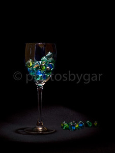 wine glass with marbles on black background