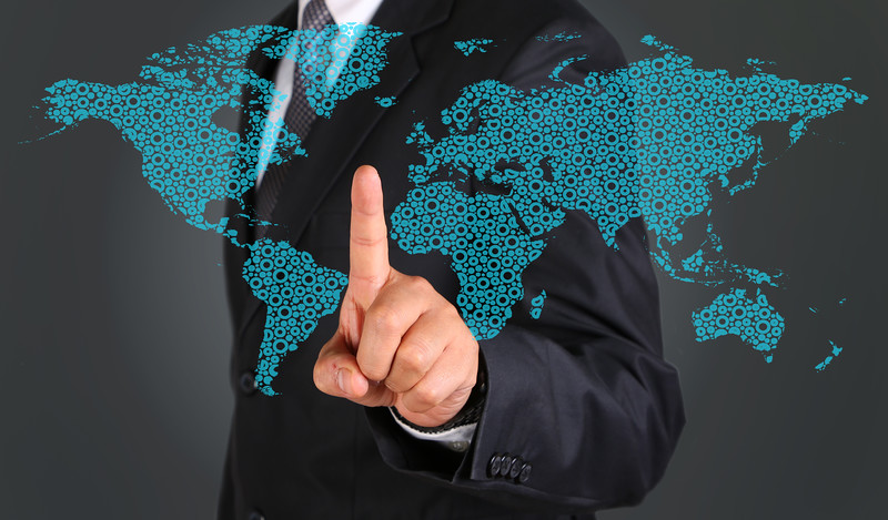 Business man touching graphic of world map.